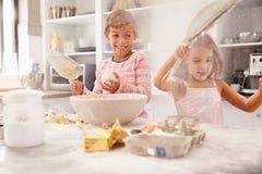 两个孩子有乐趣烘烤在厨房 免版税库存照片