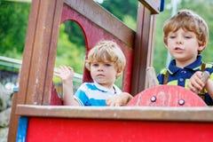 两个孩子男孩假装驾驶在操场的一辆虚构的汽车, 免版税库存照片