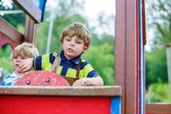 两个孩子男孩假装驾驶在操场的一辆虚构的汽车, 库存图片