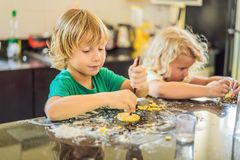 两个孩子男孩和女孩由面团做曲奇饼 库存图片