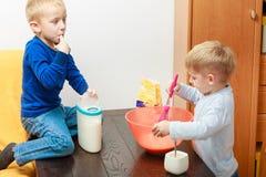 两个孩子男孩烹调,做在碗的蛋糕 免版税图库摄影