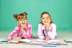 两个孩子笑和写入的玻璃 童年的概念 图库摄影
