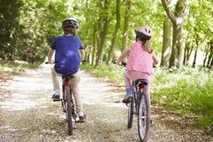 两个孩子背面图周期乘驾的在乡下 免版税库存图片
