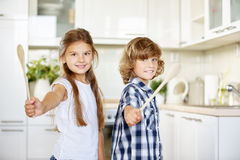 两个孩子获得乐趣在有匙子的厨房 免版税库存图片