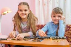 两个孩子被考虑硬币的汇集在册页的 免版税库存图片