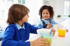 两个孩子食用早餐在学校前在厨房 库存照片