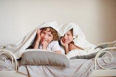 两个孩子,兄弟和姐妹,蠕动在床上在卧室 免版税库存图片