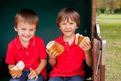 两个孩子,坐在一条被保护的长凳,吃三明治 库存照片