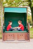 两个孩子,坐在一条被保护的长凳,演奏拍手ga 图库摄影