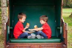两个孩子,坐在一条被保护的长凳,演奏拍手ga 库存图片