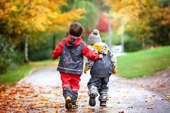 两个孩子,战斗在玩具在公园在一个雨天 库存图片