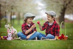 两个孩子,男孩兄弟,获得乐趣用复活节彩蛋在p 图库摄影