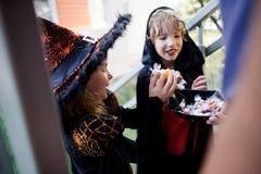 两个孩子,男孩和女孩,黑暗的服装的万圣夜作为糖果的 库存照片