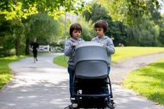 两个孩子,男孩,推挤有小婴孩的婴儿推车 免版税库存图片
