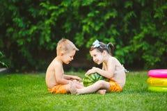 两个孩子,白种人兄弟和姐妹,坐绿草在房子后院和拥抱大鲜美甜西瓜 免版税图库摄影