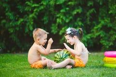 两个孩子,白种人兄弟和姐妹,坐绿草在房子后院和拥抱大鲜美甜西瓜 免版税库存图片