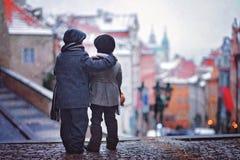 两个孩子,站立在台阶,布拉格,雪看法在他们后的 库存照片
