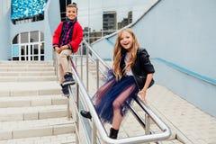 两个孩子:漂亮的孩子在街道的栏杆使用在台阶 免版税图库摄影