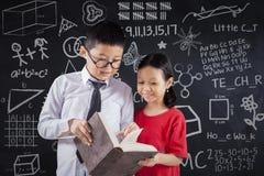 两个孩子读了在类的书 免版税库存照片