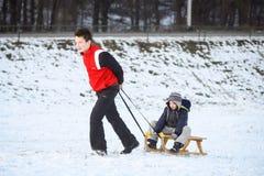 两个孩子sledding 免版税库存图片