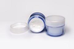 两个容器在白色背景的润湿的面霜 库存图片
