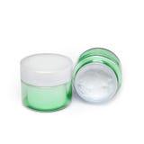 两个容器在白色背景的润湿的面霜 免版税库存照片