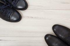 两个对在灰色木背景的黑皮革人` s鞋子 免版税库存照片