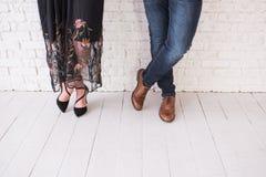 两个对在鞋子的男性和女性腿盘 结合在白色墙壁横渡腿前面的身分在鞋子 女孩 免版税库存照片