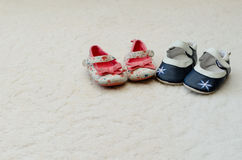 两个对女婴第一穿上鞋子与花的一蓝色在T 免版税图库摄影