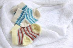 两个对婴孩袜子:蓝色和黄色镶边 免版税库存照片