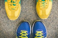 两个对明亮的体育穿上鞋子在彼此前面的身分 免版税库存图片