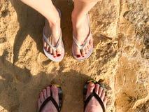 两个对有修指甲的在拖鞋,与手指的一只脚男性和女性腿在一个石含沙地板,地球上的啪嗒啪嗒的响声,是 免版税库存图片