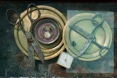 两个对老生锈的金属剪与在圆的板材的开放刀片在一块方形的玻璃下,在有白色拨号盘的古色古香的时钟附近 免版税图库摄影