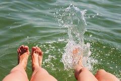 两个对脚飞溅在水中 免版税库存图片