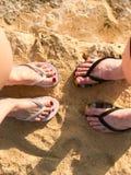 两个对腿男性和女性有一美好的修脚的在拍击在海一种热带手段的在沙子在海滩a 图库摄影