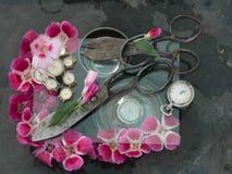两个对黑古色古香的剪刀黏附了入彼此在桃红色和绯红色花,在一块透明玻璃的白色手表中 免版税库存图片