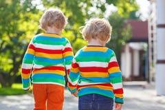 两个小兄弟姐妹孩子在五颜六色的衣物走的手上  免版税库存图片