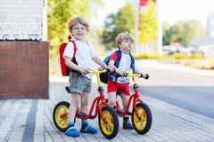 两个小兄弟姐妹孩子获得在自行车的乐趣在城市, outdoo 图库摄影