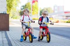 两个小兄弟姐妹孩子获得在自行车的乐趣在城市, outdoo 免版税库存照片