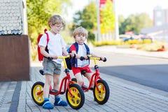 两个小兄弟姐妹孩子获得在自行车的乐趣在城市, outdoo 免版税图库摄影