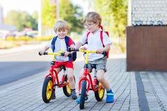 两个小兄弟姐妹孩子获得在自行车的乐趣在城市, outdoo 库存照片