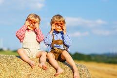 两个小兄弟姐妹男孩和朋友坐干草堆和ea 免版税库存照片