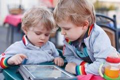 两个小兄弟姐妹男孩获得乐趣与片剂个人计算机一起 免版税图库摄影