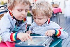 两个小兄弟姐妹男孩获得乐趣与片剂个人计算机一起 库存照片