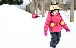 两个小双女孩充当雪 穿戴在冬天 免版税库存照片