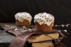 两个小复活节蛋糕和一根杨柳枝杈在黑暗的木背景 免版税库存照片