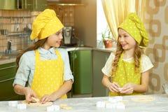 两个小女孩做酥皮点心 免版税图库摄影
