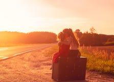 两个小女孩剪影在葡萄酒手提箱坐Th 免版税图库摄影