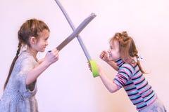 两个小女孩在剑战斗 定调子 图库摄影