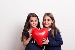两个小女孩在演播室,拿着在他们前面的一个红色心脏气球 库存照片
